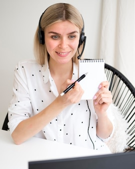 Online verre cursussenstudent die haar notitieboekje toont