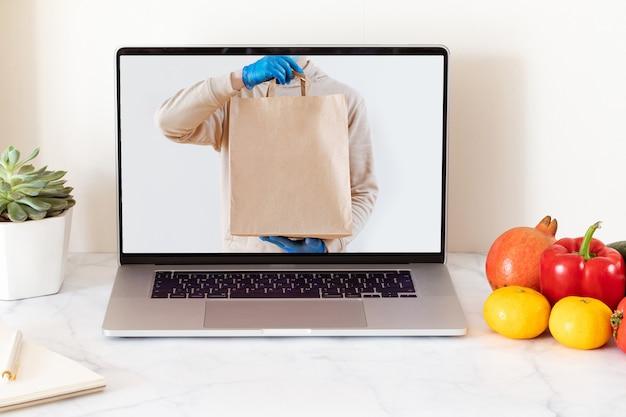 Online voedselbezorgingsconcept met witte laptop met leeg scherm. boodschappen bezorgservice. thuiskantoor.