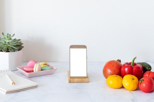 Online voedselbezorgingsconcept met witte lege scherm mobiele telefoon. boodschappen bezorgservice. thuiskantoor.