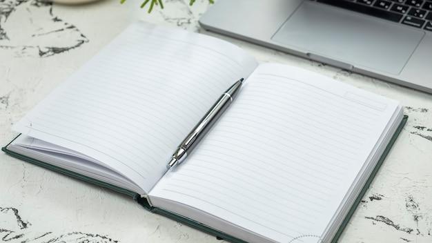 Online werk en studieconcept: notitieboekje, pen en laptop.