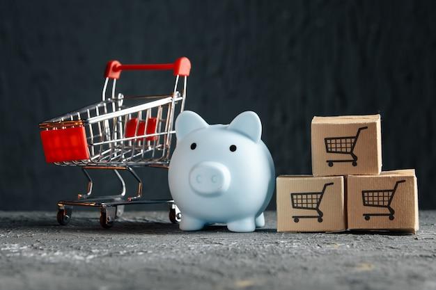 Online winkelconcept. blauwe spaarvarken met supermarktkarretje en bezorgdozen.