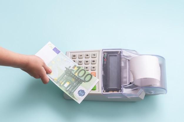 Online winkelconcept. close-up van de hand van een kind met een biljet van 100 euro boven de kassa op een blauwe achtergrond, bovenaanzicht, kopieerruimte.