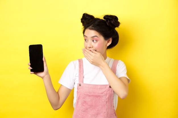 Online winkelconcept. dom japans meisje met schoonheidsmake-up, bedek de mond met de hand lachend en laat een leeg smartphonescherm zien, laat grappige dingen zien op de telefoon, geel.