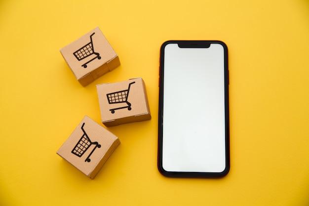 Online winkelconcept. dozen en smartphone geïsoleerd op gele achtergrond
