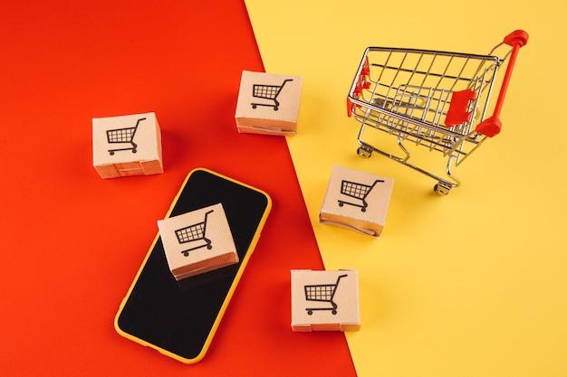 Online winkelconcept. dozen op smartphone en winkelwagentje op kleurrijk.