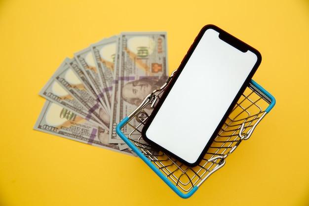 Online winkelconcept. geld, mand en smartphone geïsoleerd op gele achtergrond