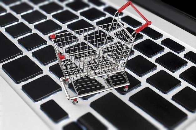 Online winkelconcept met 3d-rendering winkelwagentje op toetsenbord