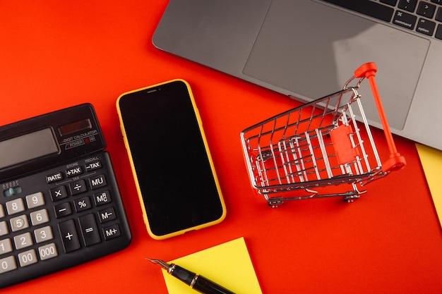 Online winkelconcept met kar dichtbij smartphone en laptop. e-commerce markt. transport logistiek. zakelijke detailhandel.