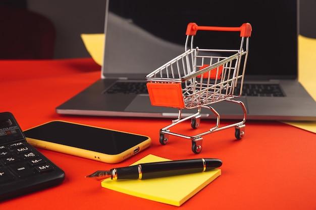 Online winkelconcept met kar en smartphone met laptop. e-commerce markt. transport logistiek. zakelijke detailhandel.