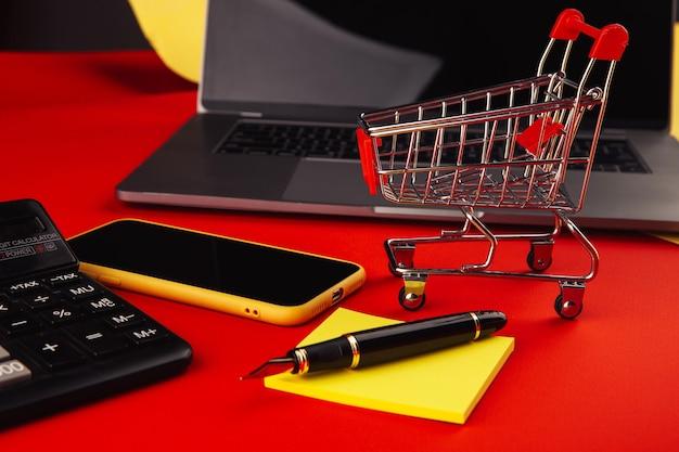 Online winkelconcept met kar en smartphone met laptop