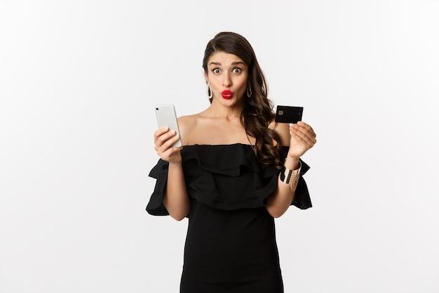 Online winkelconcept. modieuze vrouw in zwarte jurk, creditcard met smartphone vasthoudend, opgewonden kijkend, staande op een witte achtergrond.