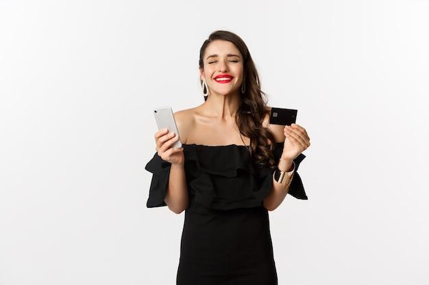 Online winkelconcept. modieuze vrouw in zwarte jurk, met creditcard met smartphone, tevreden kijkend, staande op een witte achtergrond.