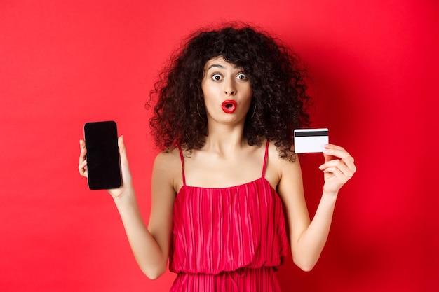 Online winkelconcept. mooie vrouw in rode jurk en lippenstift, met leeg telefoonscherm en plastic creditcard, staande op studio achtergrond.