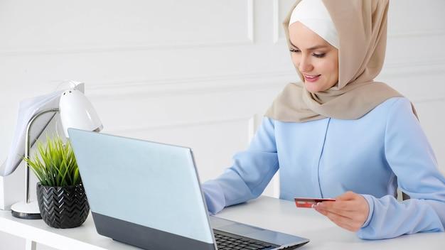 Online winkelconcept. portret van moslim jonge vrouw in beige hijab en traditionele blauwe jurk koopt online met een creditcard en laptop.