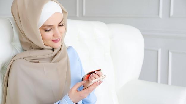 Online winkelconcept. portret van moslim jonge vrouw in beige hijab en traditionele blauwe jurk koopt online met een creditcard en mobiele telefoon zittend op een bank in de woonkamer thuis.