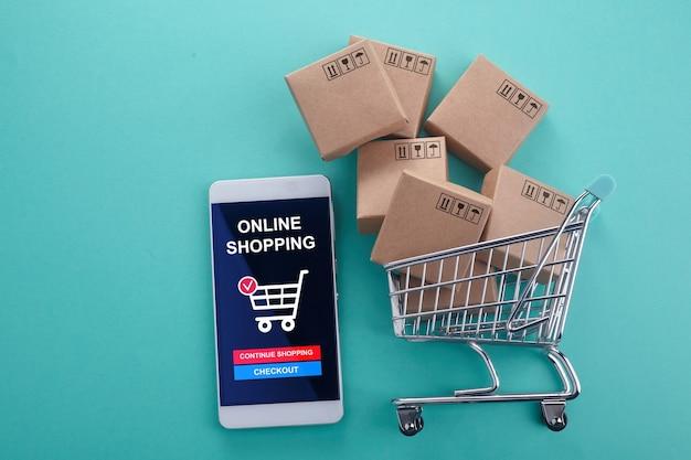 Online winkelconcept. slimme telefoon met winkelwagentje op munt achtergrond. bovenaanzicht.