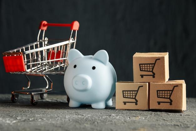 Online winkelconcept. spaarvarken met supermarktwagen en bezorgdozen