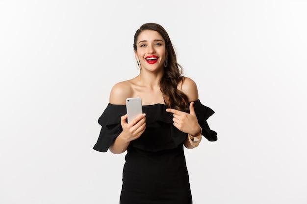 Online winkelconcept. tevreden mooie vrouw in zwarte jurk, glimlachend blij en wijzend op mobiele telefoon, staande op witte achtergrond.