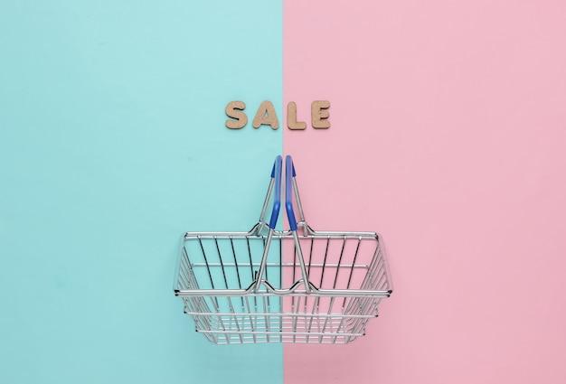 Online winkelconcept verkoop mini winkelmandje op roze blauwe pastel achtergrond