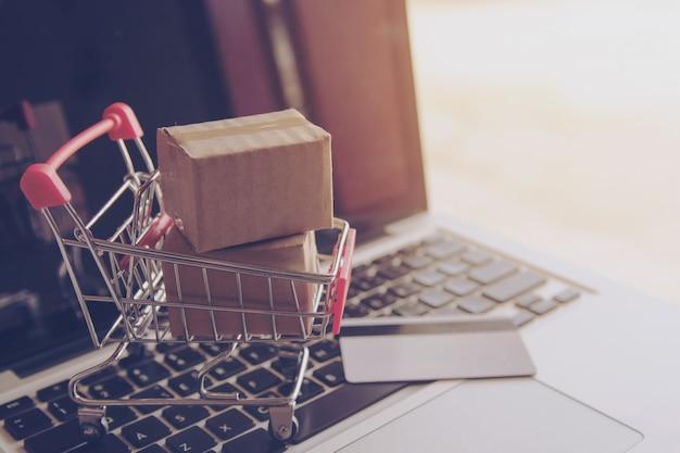 Online winkelconcept - winkelen op het online-web. kartons met een winkelpin