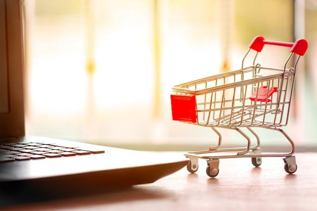 Online winkelconcept. winkelwagen, kleine dozen, laptop op het bureau