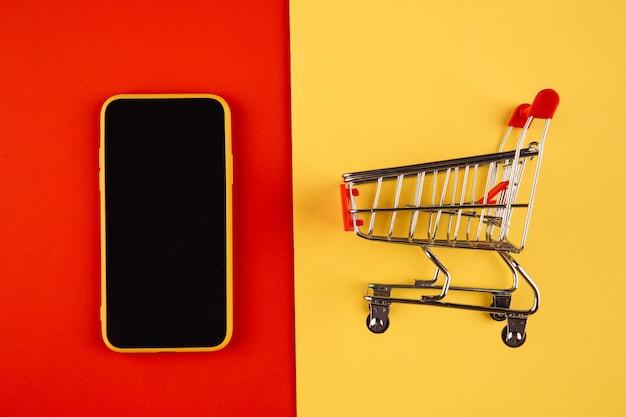 Online winkelconcepten met modelkarretje en smartphone op geel rood.