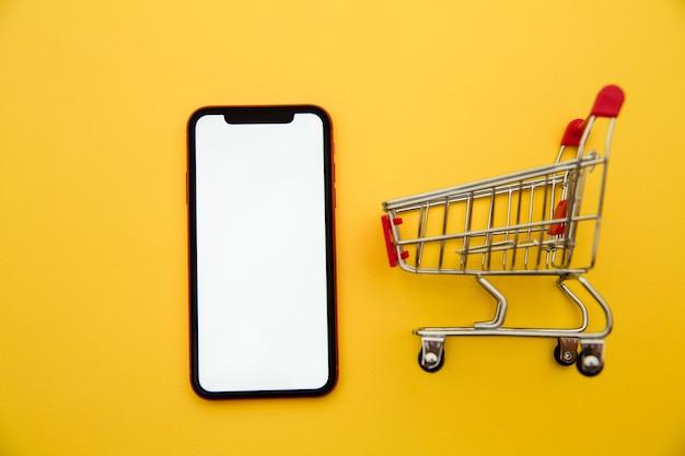Online winkelconcepten met modelkarretje en smartphone op gele achtergrond. e-commerce markt. transport logistiek. zakelijke detailhandel.