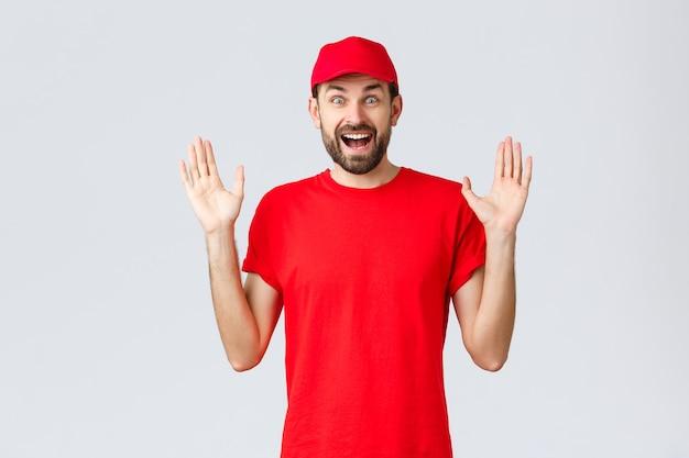 Online winkelen, bezorgen tijdens quarantaine en afhaalconcept. gelukkig vrolijke koerier in rood t-shirt en pet, bedrijfsuniform, handen omhoog verrast en geamuseerd, staande grijze achtergrond