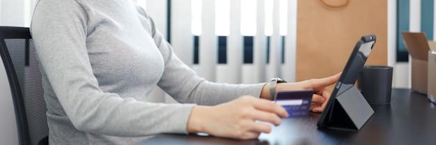 Online winkelen concept een jonge vrouw die haar creditcard gebruikt om een online aankoop in een online winkeltoepassing te vergemakkelijken.