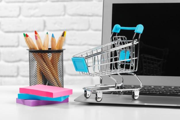 Online winkelen concept: mini-winkelwagentje en laptop