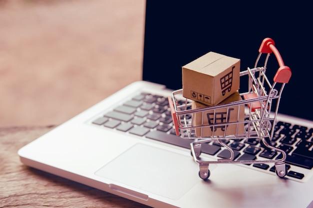 Online winkelen concept - pakket of papier dozen met een winkelwagentje logo in een trolley op een laptop toetsenbord. boodschappenservice op het online web. biedt levering aan huis.