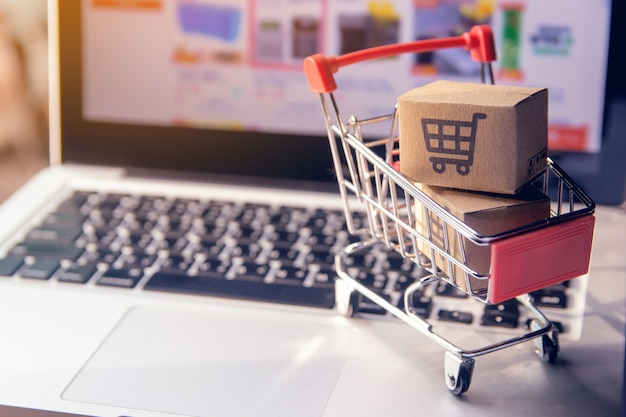 Online winkelen concept - pakket of papieren dozen met een winkelwagentje-logo in een trolley op een laptop toetsenbord. boodschappenservice op het online web. biedt thuisbezorging.