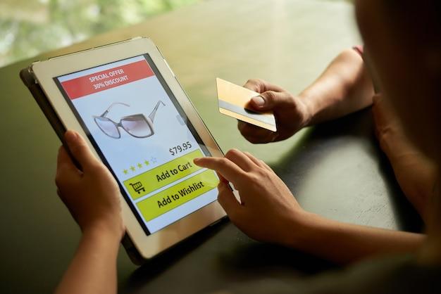 Online winkelen concept van twee onherkenbare mensen die een zonnebril toevoegen aan winkelwagen op de tablet-pc