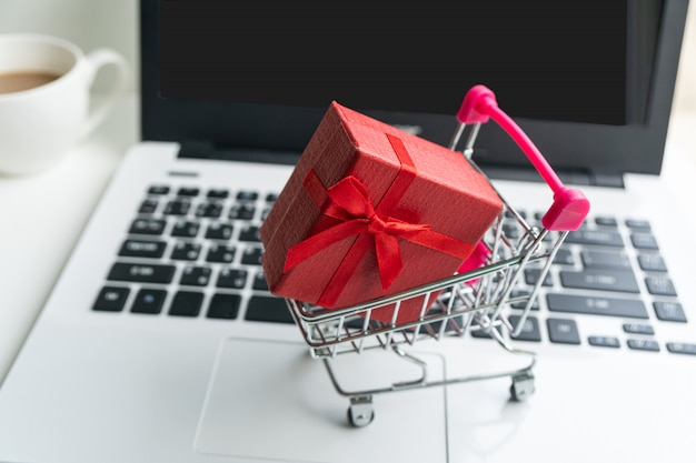 Online winkelen concept. winkelwagen, kleine doos, laptop, op het bureau, kopie ruimte, close-up