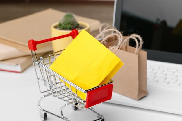 Online winkelen concept. winkelwagen, laptop op het bureau