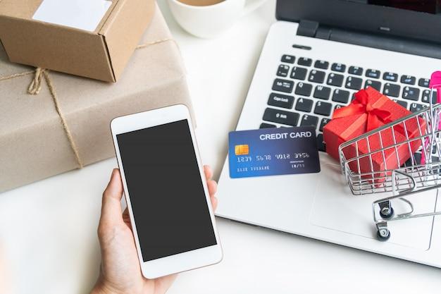 Online winkelen concept. winkelwagen, pakjes, laptop, mobiele telefoon, creditcard op het bureau thuis. bovenaanzicht, kopie ruimte