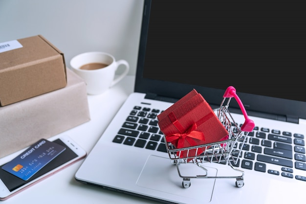 Online winkelen concept. winkelwagen, pakketdozen, laptop, creditcard op het bureau thuis. bovenaanzicht, kopieer ruimte
