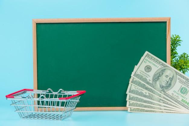 Online winkelen, een dubbele kar geplaatst op een groen bord op een blauw. Gratis Foto