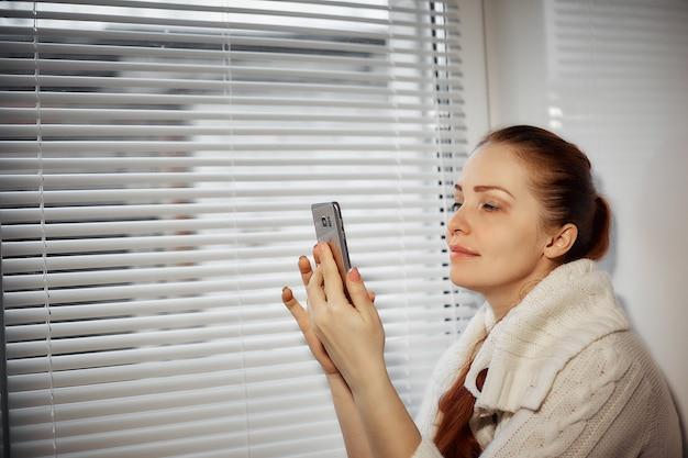 Online winkelen, een jonge vrouw die de goederen in de online winkel op het smartphonescherm doorbladert.