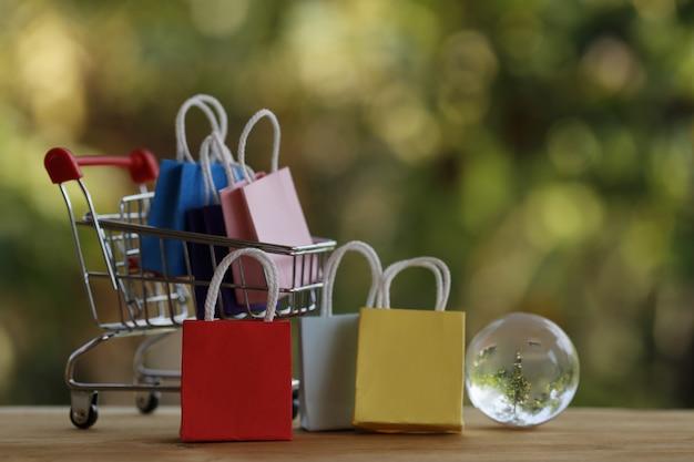 Online winkelen en e-commerce concept: papieren zak in een winkelwagentje en kristallen bol. online winkels worden beschouwd als een ander medium om goederen tussen ondernemers en klanten te verhandelen.