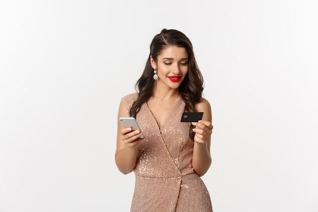 Online winkelen en kerstconcept. elegante jonge vrouw betalen voor internetaankoop met smartphone en creditcard, staande in luxe jurk op witte achtergrond