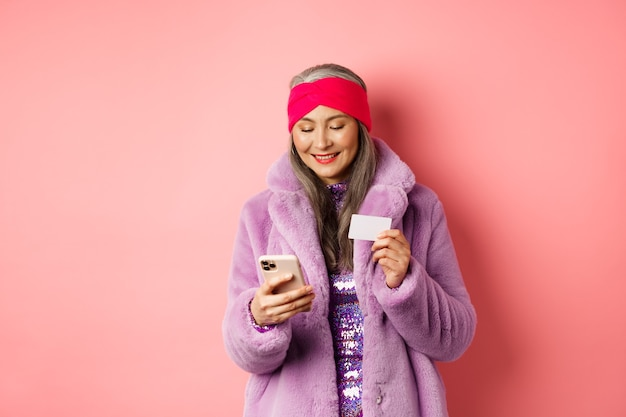 Online winkelen en mode concept. stijlvolle aziatische oudere vrouw die in een modieuze paarse jas staat en op smartphone betaalt, met plastic creditcard, roze achtergrond.