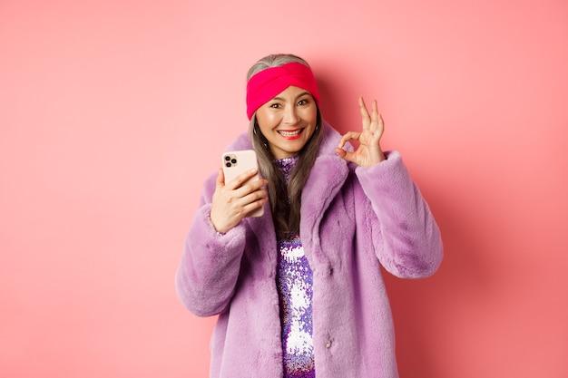 Online winkelen en mode concept. stijlvolle aziatische senior vrouw die een goed teken toont en een mobiele telefoon vasthoudt, die internetwinkel, roze achtergrond aanbeveelt