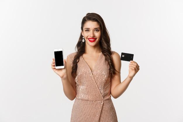 Online winkelen en vakantie concept. aantrekkelijke vrouw in feestjurk met creditcard en mobiel scherm, glimlachend gelukkig, witte achtergrond