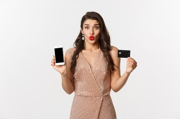 Online winkelen en vakantie concept. opgewonden mooie dame in elegante jurk met mobiel scherm en creditcard, staande op een witte achtergrond.
