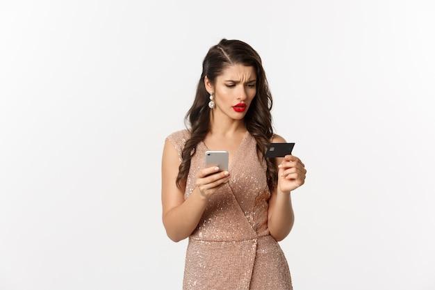 Online winkelen en vakantie concept. stijlvolle vrouw in elegante jurk, verward kijkend naar creditcard tijdens het betalen op mobiele telefoon, witte achtergrond.