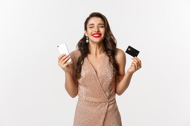 Online winkelen en vakantie concept. tevreden en gelukkige vrouw in elegante jurk glimlachend, met creditcard en mobiele telefoon, staande op een witte achtergrond.