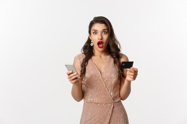 Online winkelen en vakantie concept. verrast vrouw in glamour jurk, internet kopen met creditcard en mobiele telefoon, verbaasd kijken, witte achtergrond.