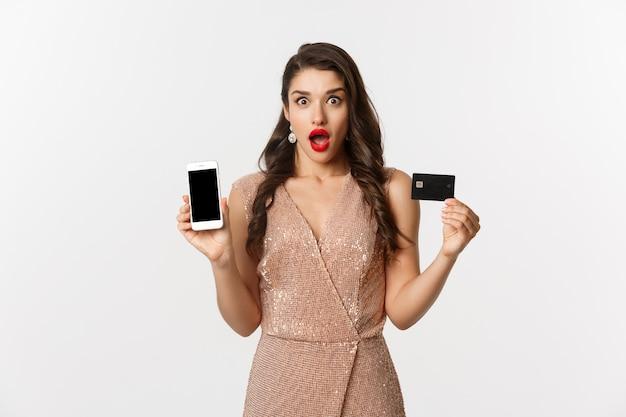 Online winkelen en vakantie concept. vrouw die verbaasd kijkt en creditcard toont met smartphonescherm, staande op een witte achtergrond.