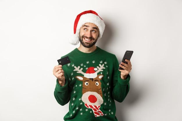 Online winkelen en wintervakantie concept lachende man denken en houden creditcard met mobiele...